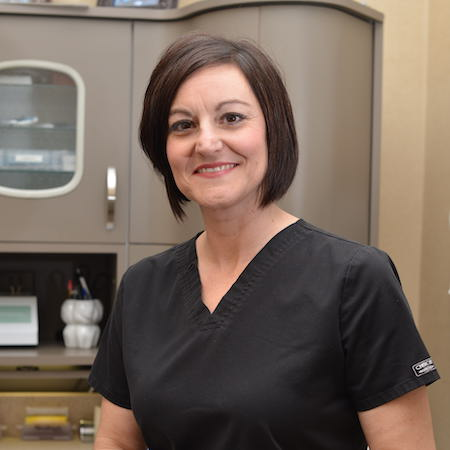 Brandie our Dental Assistant wearing a black uniform, with short brown hair, and smiling