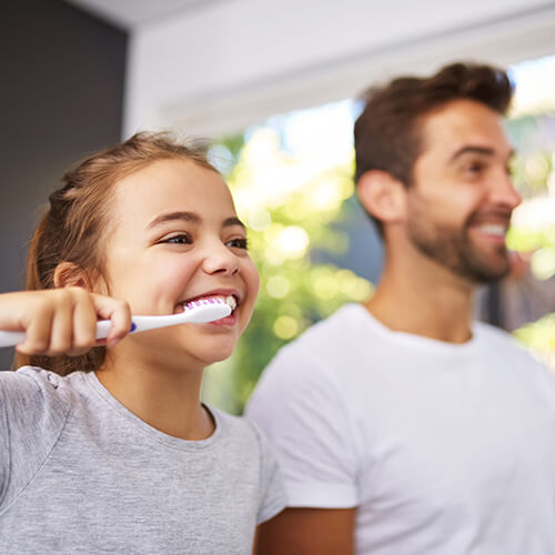 A dad and his daughter brushing their teeth together to show that your Durham dentist is focused on prevention.