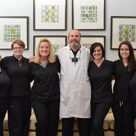 Dr. Stead Willis DMD, a Durham NC dentist, standing in a line with his dental team