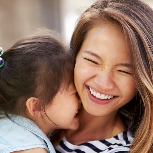 Young mum wearing a stripy top hugging her young daughter and laughing