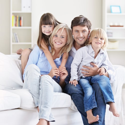 Family of four sitting on a white sofa, embracing, and smiling