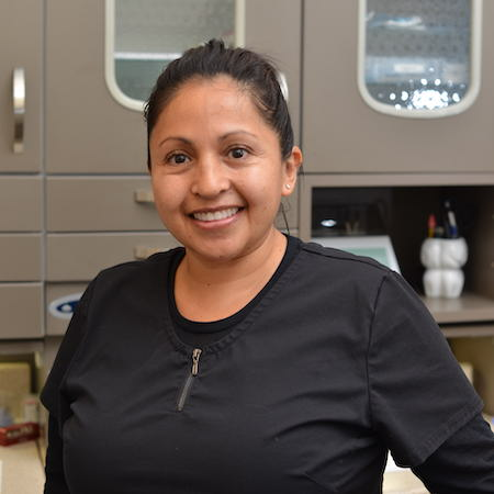 Lupe our Dental Assistant standing in a dental lab with dark hair tied back and smiling