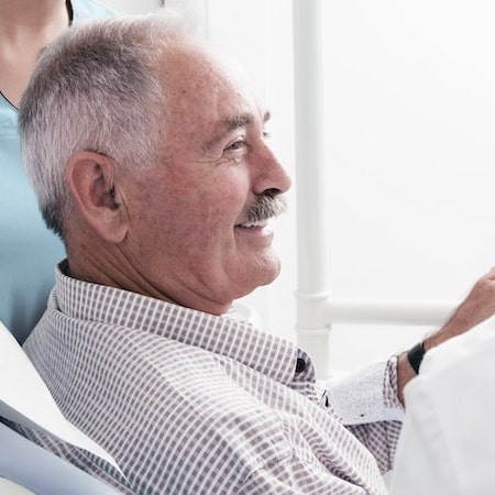 Side profile of an older man sitting in a dental chair and smiling while wearing a shirt