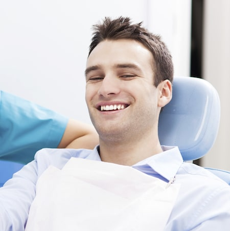 Young man sitting in a treatment chair wearing a dental bib and smiling