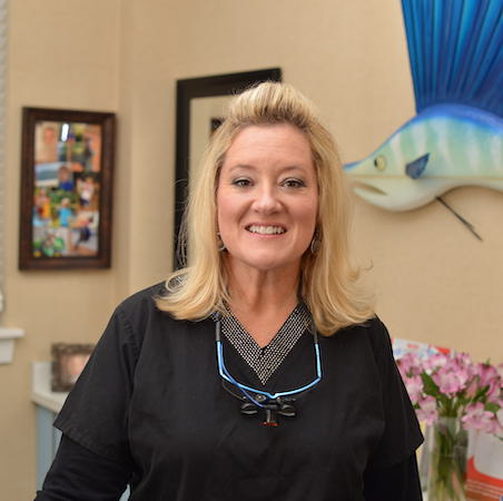 Michelle our Dental Hygienist with shoulder length blond hair, smiling at the camera