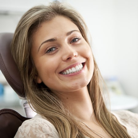 Young woman with long brown hair sitting in a dental chair and smiling
