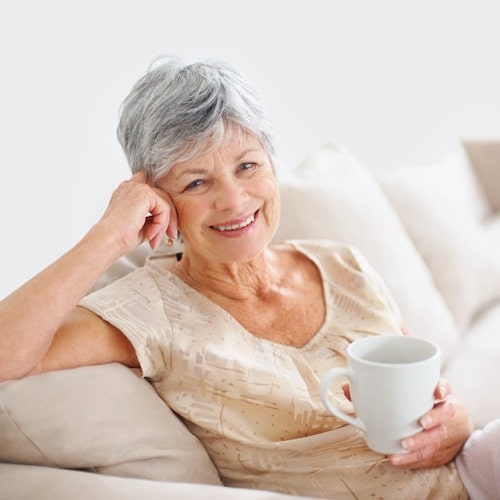 Mature woman sitting on a sofa while holding a cup, leaning on her left hand, and smiling