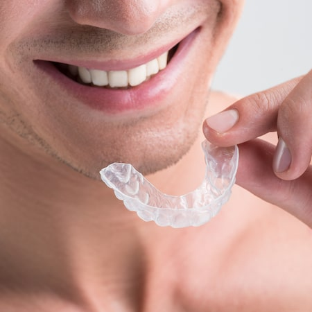 Close up of a man putting in a clear mouthguard