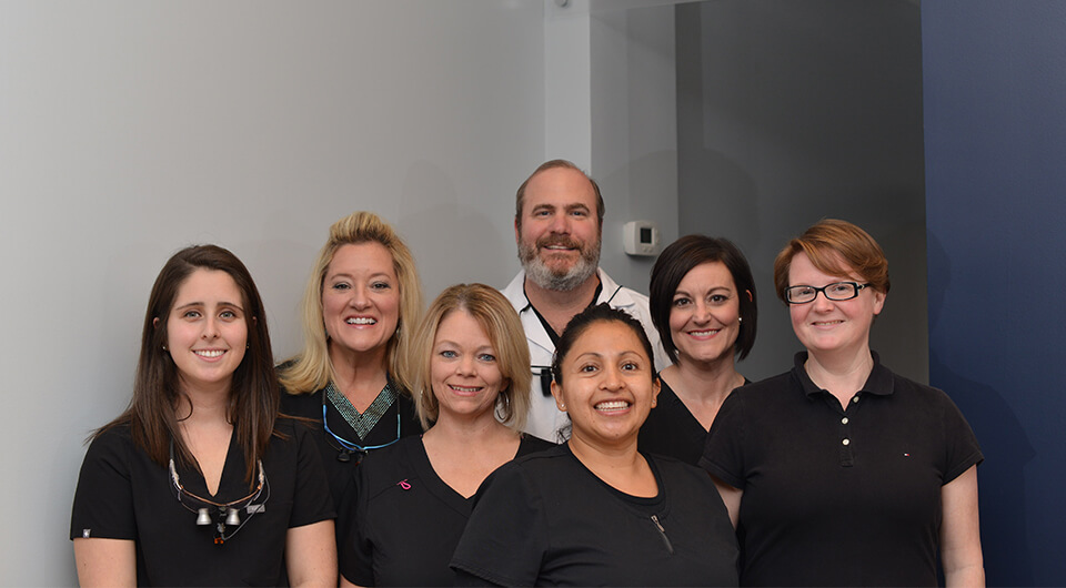 Shot of Dr. Stead Willis an his dental staff smiling at our office entrance