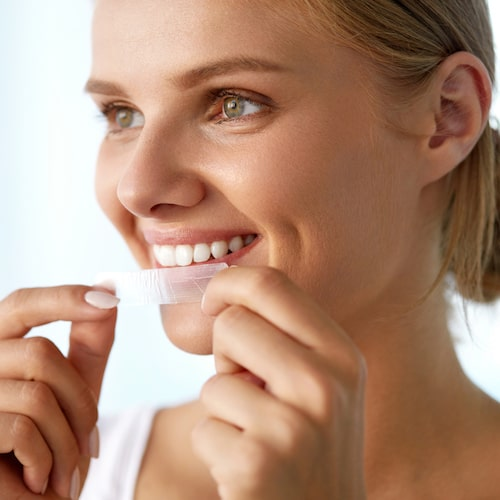 Woman smiling about to put on a teeth whitening strip on her teeth