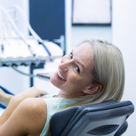 Older women lying in a dental chair looking back and smiling