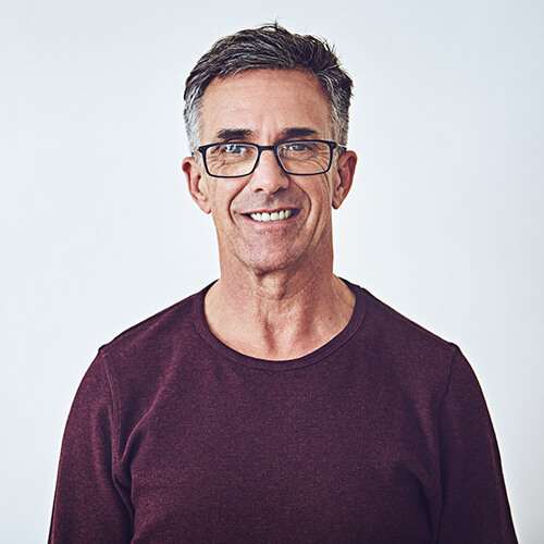 A man with glasses and red shirt smiling