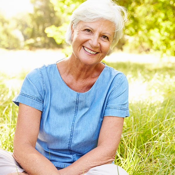 An older woman smiling and showing off her natural-looking dental implants from Stead Willis DMD