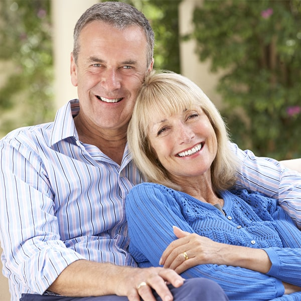 An older couple smiling after getting dental implants in Durham, NC