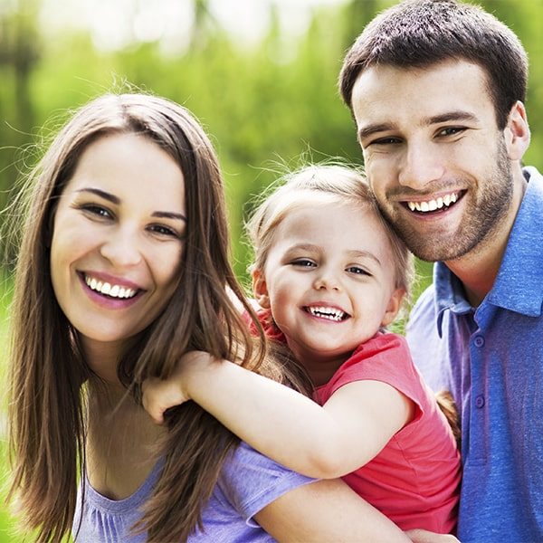 A family of three together and smiling after oral hygiene cleanings in Durham, NC