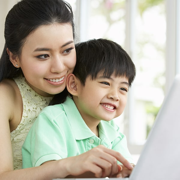 A mother and son looking up oral hygiene cleanings on laptop in Durham